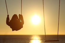 Lonely woman silhouette swinging at sunset on the beach.jpg