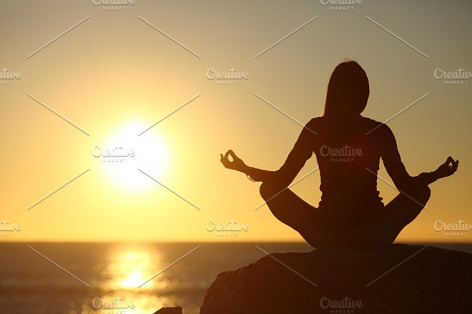 Woman meditating and practicing yoga watching the sun.jpg - Health