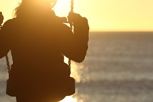 Woman silhouette swinging at sunset on the beach.jpg