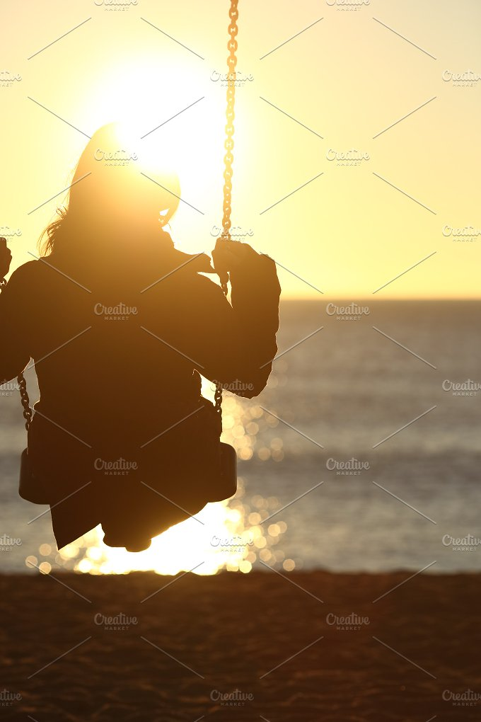 Woman silhouette swinging at sunset on the beach.jpg - People
