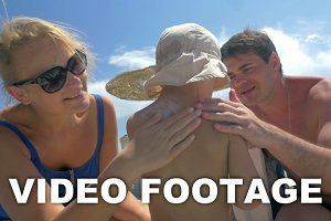 Parents applying suntan lotion