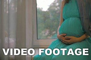 Pregnant woman sitting on windowsill