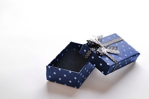 Small open blue gift box with ribbon