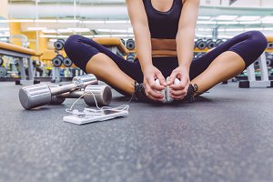Sporty woman sitting with dumbbells