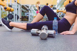 Sporty woman resting sitting in gym