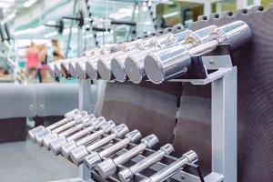 Rows of metal dumbbells in gym
