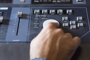 hand adjusting a sound mixing desk
