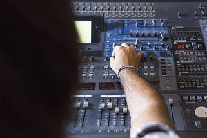 sound engineer adjusting sound desk