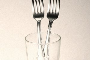 Two forks standing inside a glass