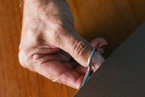 Man cutting cardboard with scissors