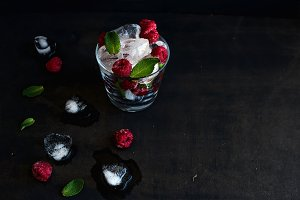 frozen raspberry in glass and ice