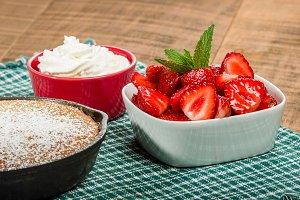 Bowl of strawberries cake and cream