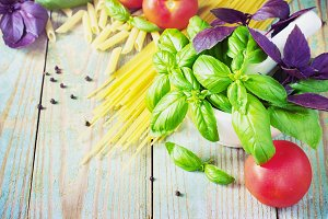 Pasta, tomatoes, and basil on wooden background