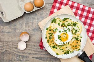 Potatoes and fried egg with parsley
