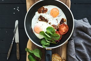 Pan of fried eggs, bacon & tomatoes