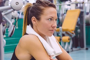 Woman with towel resting in the gym