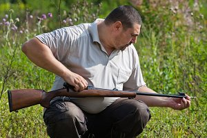man cleans the barrel of rifle