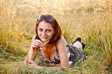Girl in field smelling flower