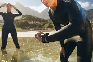 Athletes in wet suits checking timer