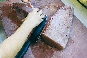 Cook cleaning a tuna loin