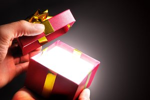Hands opening a red gift box