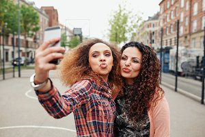 Beautiful pouting women taking photo
