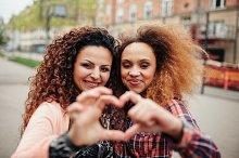 Young women making heart shape