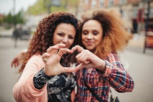 Friends making heart shape gesture
