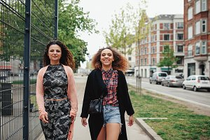 Two girlfriends walking in city