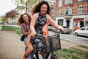 Two young girls having fun on bike
