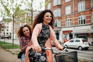 Cheerful young friends riding a bike