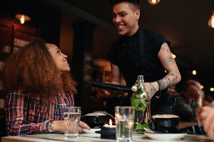 Woman talking to waiter at cafe