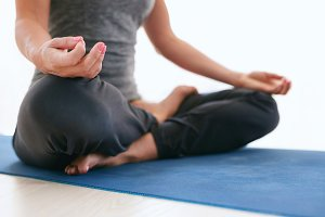Woman in Lotus pose on exercise mat