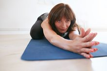 Fitness trainer doing yoga at gym