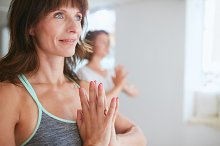 Women in tree pose yoga with Namaste