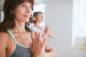 Women in tree pose yoga with Namaste
