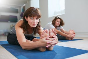 Women doing paschimottanasana yoga