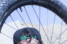 boy fixing the BMX bike wheel