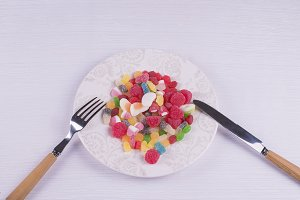 Plate  full of candies.Fork Knife