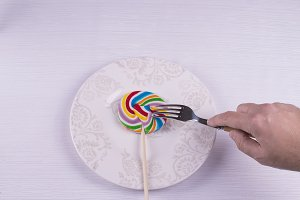 Hand with a fork click on a lollipop