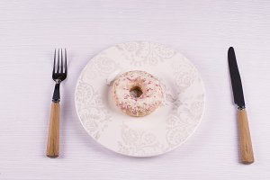 Donut on a plate with eating utensil