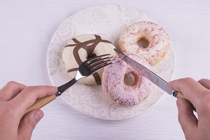 Hands with eating utenils and donuts
