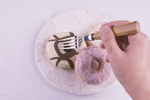 Hand with a fork andchocolate donut