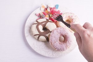 Hand clicking candies with donuts