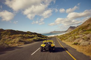 Couple driving in small beach buggy