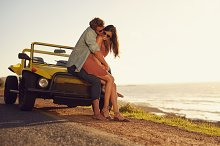 Young couple in love on hood of car