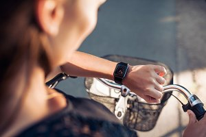 Woman with a bike looking at watch