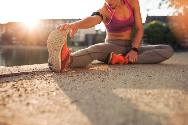 Female athlete stretching legs
