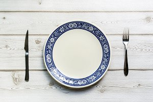 knife and fork and plate on wooden b