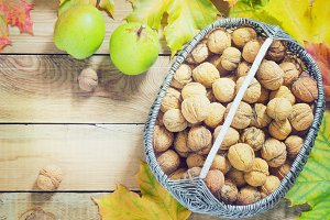 Autumn leaves walnuts over old wooden background